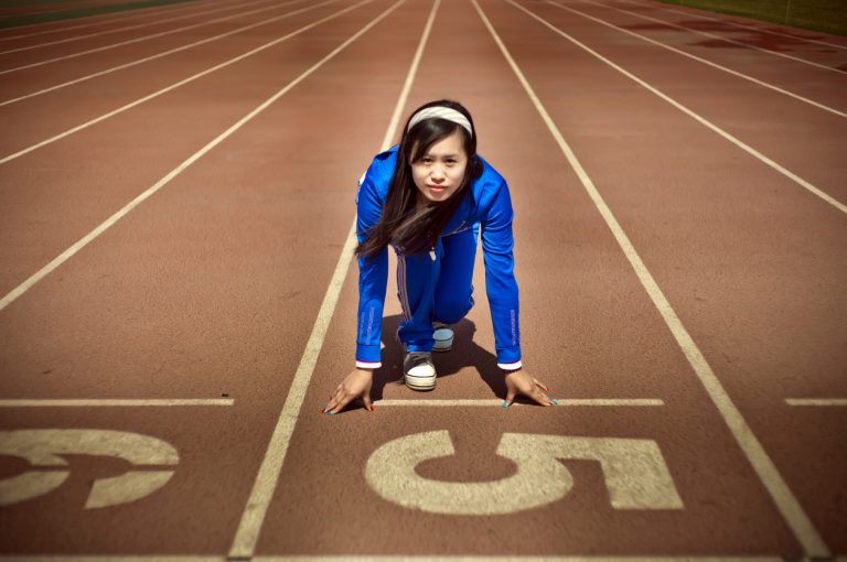 East asian woman on track starting to run